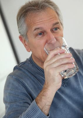 Senior man drinking glass of water