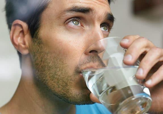 Homme buvant de l'eau du robinet